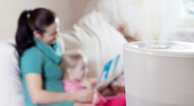 Mother reading book to her daughter on the background of humidif