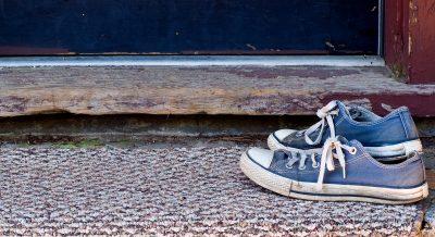 Blue Tennis Shoes on Door Mat