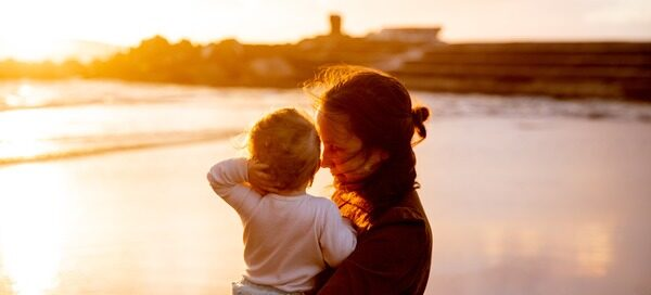 mom carrying child looking at sunset