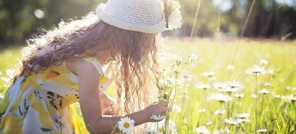 Girl bending to a flower