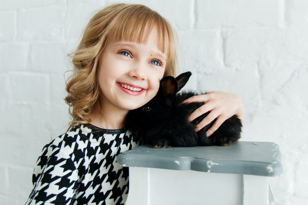 Girl holding tight to a rabbit