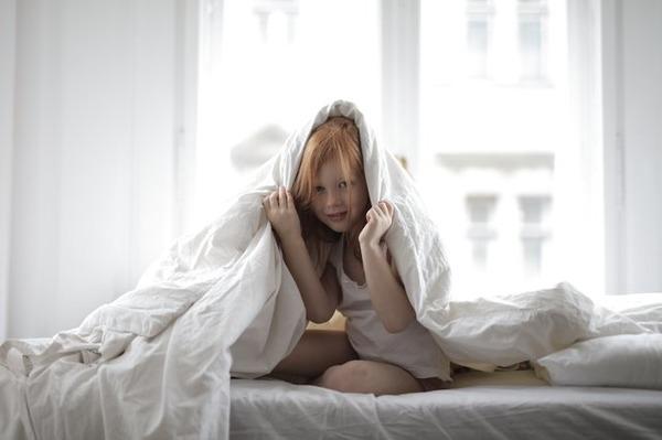 Girl under bedsheets feeling sick